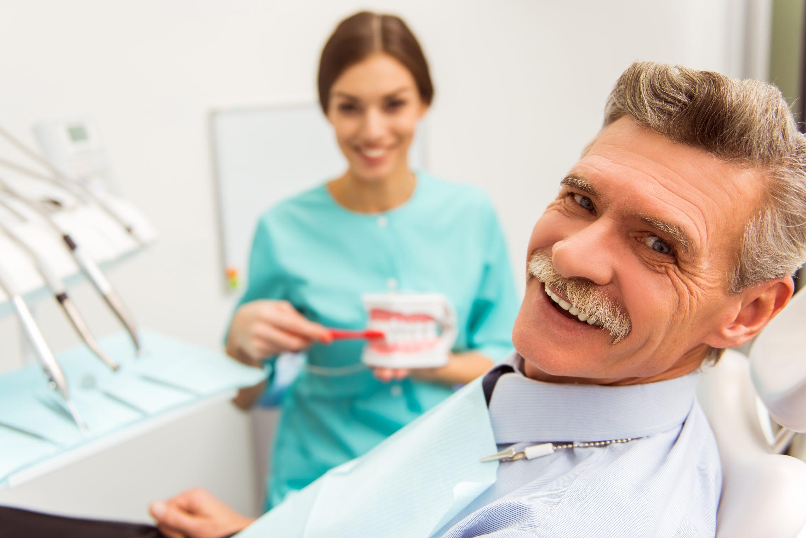 Elderly man smiling in dental chair.