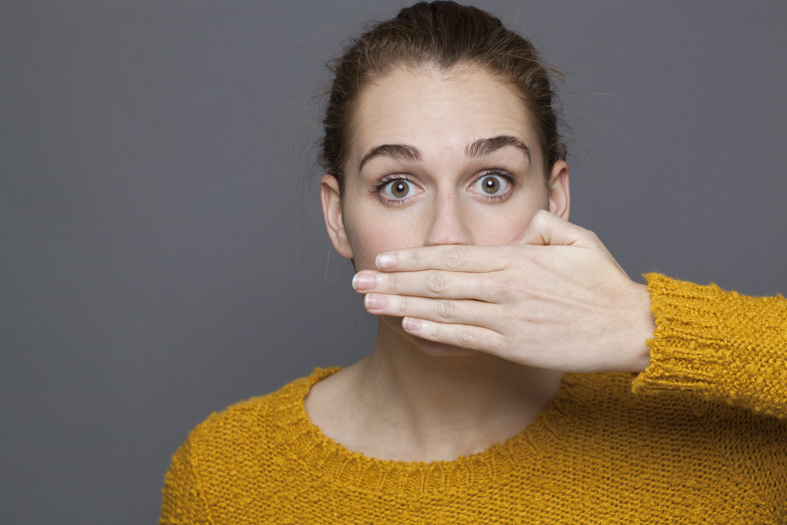 Gum disease causes woman to cover her mouth with her hand.