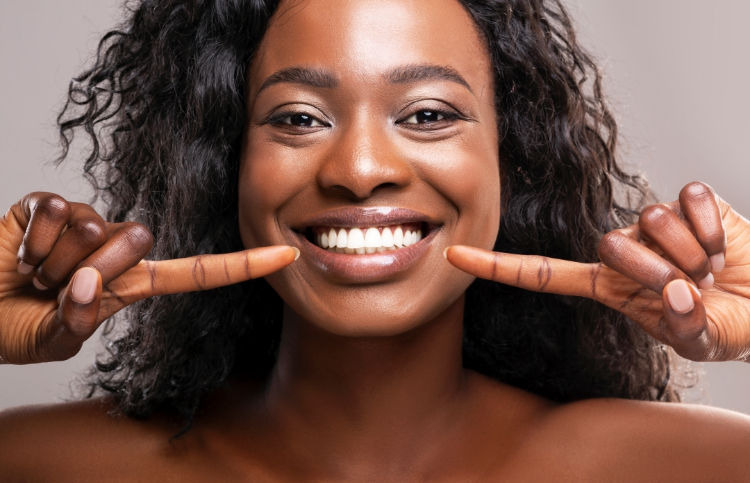 A woman is happy about cosmetic dentistry and is pointing to her smile